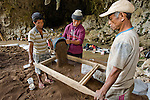 Local Manggarai workers sift through excavated soil spit-by-spit in search of tiny remains at Liang Bua cave, , discovery site of the Flores hobbit, Homo floresiensis