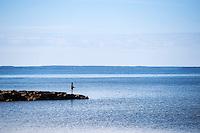 Boy fishing from a jetty, Cape Cod, Wellfleet, Massachusetts, USA
