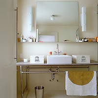 The vanity unit in the bathroom is a combination of slate and steel tubing