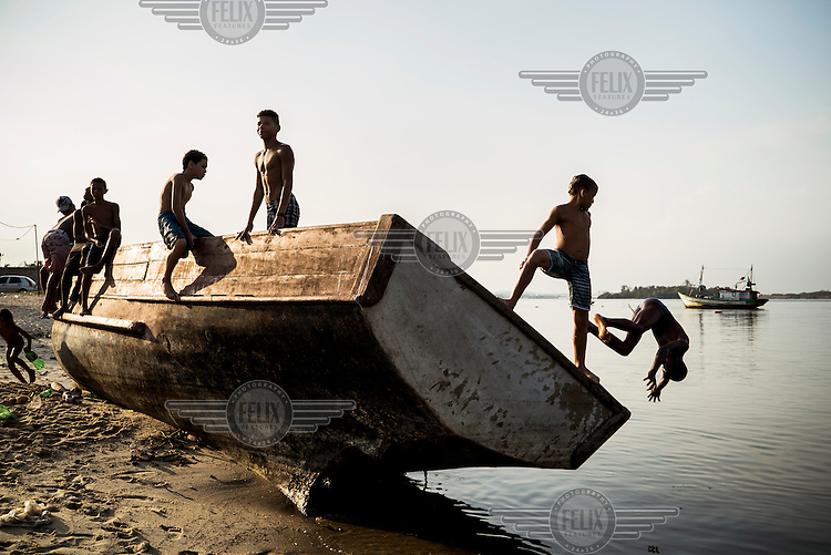 A group of boys leap from the wreckage of a fishing boat on Guanabara Bay. The bay's water, where 70 percent of the city's sewage is dumped, was declared too polluted for swimmers to use in 2001. They now use the parrallel Piscinao de Ramos (big pool of Ramos), an artificial pool built beside the bay by the state of Rio de Janeiro to give North Zone residents clean water to enjoy. It holds 30 million litres of filtered and chlorinated seawater and can attract 80,00 visitors over a single, sweltering hot weekend. Despite its popularity, the piscinao (big pool) is controversial. Some north region residents believe it was built to keep them away from the luxurious south zone beaches. Nonetheless, thousands of people who live in the surrounding favelas visit throughout the summer.