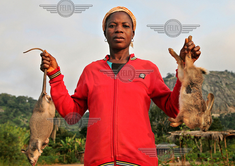 A woman selling bush rat and rabbits on a roadside.