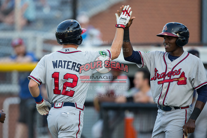 Jan Carlos Encarnacion (right) of the Danville Braves high fives teammate Drew Waters (12) as he crosses home plate after hitting a 3-run home run against the Burlington Royals at Burlington Athletic Stadium on August 14, 2017 in Burlington, North Carolina.  The Royals defeated the Braves 9-8 in 10 innings.  (Brian Westerholt/Four Seam Images)