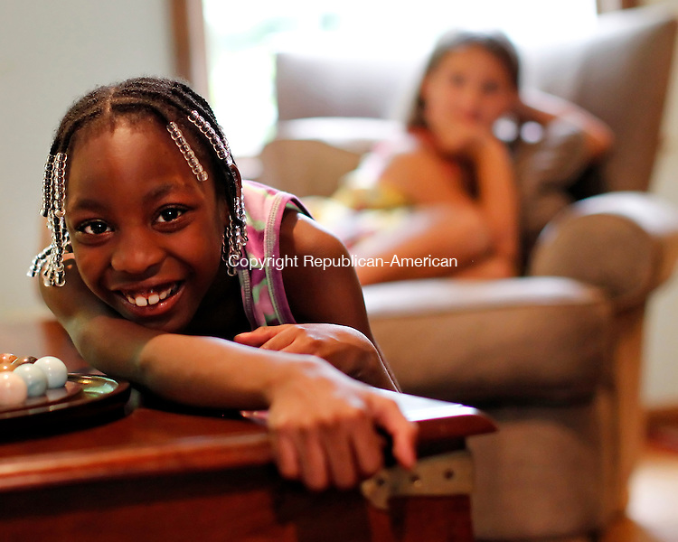 Southbury, CT-14, July 2010-071410CM12  Margy Dowleyne, 8, of Brooklyn, NY plays inside the living room of the Navas' home in Southbury.  In the background is Jacqueline Navas, 9.  Dowleyne spent a week with the Navas through the Fresh Air Fund. The agency, a not-for-profit, provides summer experiences for children.  Dowleyne had the opportunity to get away from the city life, and spend a week in the country.   --Christopher Massa Republican-American