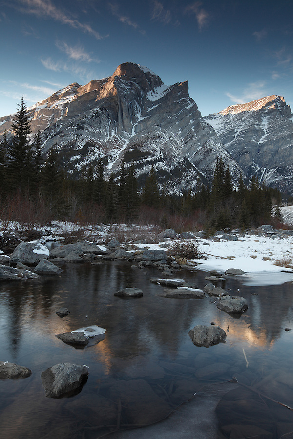 Mt. Kidd is seen reflected in a small pool surrounded by ice and snow in the Kananaskis country area of Alberta, Canada.