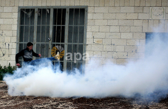 A Palestinian protester kicks back a tear gas canisters fired by Israeli soldiers during a demonstration against the expropriation of Palestinian land by Israel in the village of Kfar Qaddum, near the West Bank city of Nablus, on March 2, 2012.  Photo by Wagdi Eshtayah