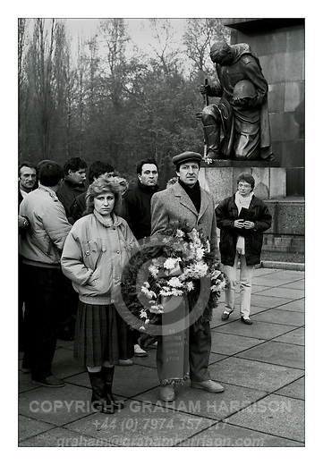 "Delegation of an East German Friendship Train with a wreath ""In honour of the fallen Soviet Heroes"" at the monument to the Red Army at Treptower Park, East Berlin, 18 November 1989. The monument is dedicated to 5,000 of the 80,000 Soviet soldiers who fell in the Battle of Berlin in April- May 1945. Friendship Trains carried the elite of East Germany's Young Pioneers and Ernst Thälmann Pioneers to Socialist countries to foster international relations. This group 9301/170 USSR may have traveled to the Soviet Union in 1967 or 1969. Photograph copyright Graham Harrison."