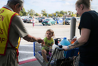 NWA Democrat-Gazette/CHARLIE KAIJO Volunteer Bob Schmitz (left) gives a Tootsie Roll to Izabella Martinez, 4, of Rogers (center) during a Tootsie Roll drive, Friday, October 5, 2018 at Walmart in Rogers.<br /><br />The Knights of Columbus is kicking off their annual tootsie rool drive Friday. The fundraiser runs through Oct. 13. They hand out Tootsie Rolls and accept donations, similar to the VFW poppy campaign.