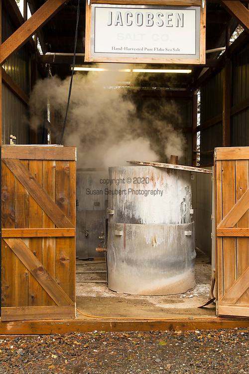 Jacobsen Salt Company in Netarts, Oregon, USA. The salt is harvested from sea water pumped from Netarts Bay in to their facility located on the shore of the bay. Jacobsen Salt was founded in 2011 by owner Ben Jacobsen.  Their main products are flake and kosher sea salts available for sale in their store in Portland, Oregon.  Contact Ben Jacobson sales@jacobsensalt.com or 503-473-3952. Pictured here are some of the outdoor tanks used for boiling sea water