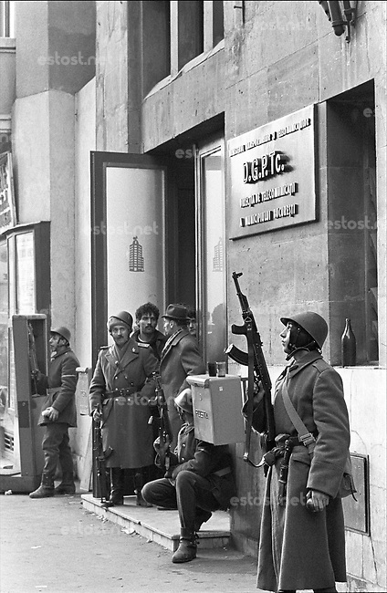 ROMANIA, Victoria Bd., Bucharest, 23.12.1989.Victoria boulevard in the centre: Main telephone central under fire. Exhausted soldiers fear bullets from tall buildings. They don't dare to eat the apples they have received..© Andrei Pandele / EST&OST