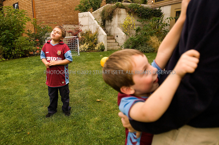 10/24/2006--Seattle, WA, USA..8 year old Clark Perry (left) plays with his father, David and Lauri Perry, and younger brother Owen (4) in the family's garden in Seattle. Clark was diagnosed with autism when he was 3 1/2 years old...Photograph By Stuart Isett.All photographs ©2006 Stuart Isett.All rights reserved.