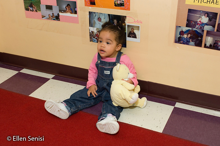 MR / Schenectady, NY.Schenectady Day Nursery / private non-profit daycare center / Toddler class.Girl (1, African-American / Caucasian) sits alone on the floor holding a stuffed animal..MR: Far3.© Ellen B. Senisi