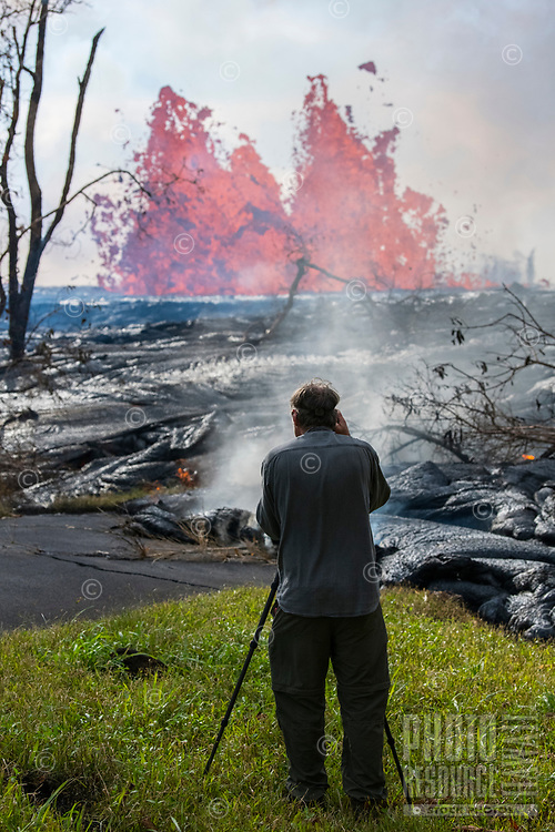 May 2018: A man takes photographs of the Kilauea Volcano eruption in Leilani Estates, Puna, Big Island of Hawai'i.