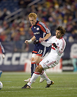 New England Revolution midfielder/defender Jeff Larentowicz (13) heads ball down as Chicago Fire midfielder Baggio Husidic (9) defends. The New England Revolution tied the Chicago Fire, 0-0, at Gillette Stadium on October 17, 2009.