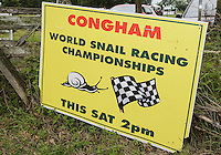 2014 World Championship Snail Racing in Congham (Norfolk)<br /> The welcoming board at the 2014 World Championship Snail Racing in Congham (Norfolk)<br /> For more than 25 years the World Snail Racing Championships have been held at Congham, near King's Lynn, in Norfolk.Before snails can enter a race a sticker with a number must be put on so they can be identified. The snails race from the centre of a circle to the outside. The circle has a radius of 13 inches. The snails are put in the middle and pointed in the right direction.The  Snail Master Neil starts the races. He shouts: &quot;Ready, steady, SLOW!&quot; And off dash the snails! The Snail Master keeps the course well-watered as snails like damp conditions.Races are held on a table covered with a white cloth. Machine a circle, with braid in the middle, and then machine a similar circle 13 inches away.Owners do dress up. The World record stands at 2 minutes over the 13 inches. It was set up in 1995 by a snail called Archie. The record can only be challenged at the World Championships at Congham.Giant foreign snails are not allowedOften owners like to give their snails names like Speedy or Schumacher!<br /> Picture by Marcello Pozzetti &copy; IPS PHOTO AGENCY<br /> Cavell Barn<br /> The Common<br /> Swardeston<br /> Norwich<br /> Norfolk<br /> NR14 8DZ<br /> T 01508 571 480<br /> M 07973308835