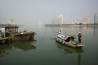 Huizhou, Guangdong province, China - Fishermen arrive with their catch on the Dong Jiang River against a backdrop of the new Huizhou financial district, October 2014.