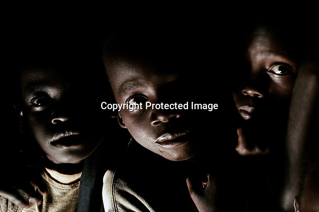 GULU, UGANDA MAY 20: Children arrive at a shelter from their villages as the sun sets on May 20, 2005 in Gulu, Uganda. They are some of about 20,000 night commuters that sleep in Gulu town every night, as they are afraid of being abducted by the Lord's Resistance Army (LRA). The rebel group has brought terror to Northern Uganda for almost twenty years, fighting the Ugandan government. The victims are usually children, which are abducted and used as child soldiers and sex slaves. Some children walk for hours from their home every day to sleep at Noah's Arch, an NGO housing children in Gulu. They are too afraid to sleep in the villages. (Photo: Per-Anders Pettersson)..