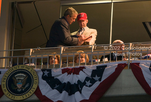 30 March 2008 - Washington, D.C. - President George W. Bush signs an autograph during the opening game for the Washington Nationals. The game is the first regular season game in the newly completed stadium. Photo Credit: Kristoffer Tripplaar/ Sipa Press