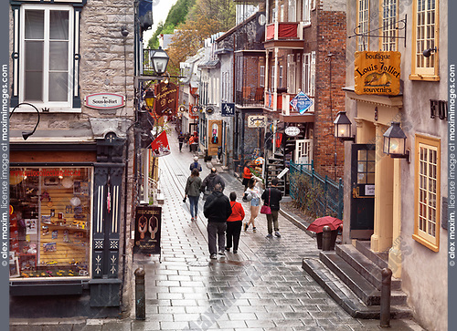 Petit Champlain historic street in old Quebec City with its colorful shop windows and restaurants. Boutique Louis Jolliet, Le Forgeron d'Or, Le Souvenoit and other stores and restaurants on a rainy day. Quebec, Canada. Rue du Petit-Champlain, Rue Sous-le-Fort, Ville de Québec.