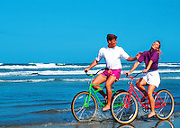 Middle-aged couple riding bikes on the beach