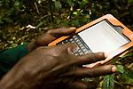 Anti-poaching snare removal team member, John Okwilo, marking location of illegally cut wood, Kibale National Park, western Uganda