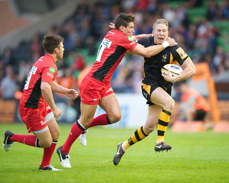 130712 Copyright onEdition 2012 ©.Free for editorial use image, please credit: onEdition..Danny Wells of London Wasps is tackled by Nils Mordt of Saracens at The Stoop, Twickenham in the first round of The J.P. Morgan Asset Management Premiership Rugby 7s Series...The J.P. Morgan Asset Management Premiership Rugby 7s Series kicked off again for the third season on Friday 13th July at The Stoop, Twickenham with Pool B being played at Edgeley Park, Stockport on Friday, 20th July, Pool C at Kingsholm Gloucester on Thursday, 26th July and the Final being played at The Recreation Ground, Bath on Friday 3rd August. The innovative tournament, which involves all 12 Premiership Rugby clubs, offers a fantastic platform for some of the country's finest young athletes to be exposed to the excitement, pressures and skills required to compete at an elite level...The 12 Premiership Rugby clubs are divided into three groups for the tournament, with the winner and runner up of each regional event going through to the Final. There are six games each evening, with each match consisting of two 7 minute halves with a 2 minute break at half time...For additional images please go to: http://www.w-w-i.com/jp_morgan_premiership_sevens/..For press contacts contact: Beth Begg at brandRapport on D: +44 (0)20 7932 5813 M: +44 (0)7900 88231 E: BBegg@brand-rapport.com..If you require a higher resolution image or you have any other onEdition photographic enquiries, please contact onEdition on 0845 900 2 900 or email info@onEdition.com.This image is copyright the onEdition 2012©..This image has been supplied by onEdition and must be credited onEdition. The author is asserting his full Moral rights in relation to the publication of this image. Rights for onward transmission of any image or file is not granted or implied. Changing or deleting Copyright information is illegal as specified in the Copyright, Design and Patents Act 1988. If you are in any way unsure of your right to publish this image pl