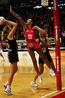 World goalkeep Geva Mentor leaps to try to block Irene Van Dyk during the International  Netball Series match between the NZ Silver Ferns and World 7 at TSB Bank Arena, Wellington, New Zealand on Monday, 24 August 2009. Photo: Dave Lintott / lintottphoto.co.nz