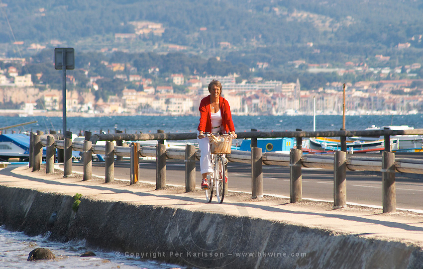 Susanne Wadesten in red and white on a bicycle, riding along the sea Clos des Iles Chambres d'Hotes Bed and Breakfast Le Brusc Six Fours Cote d'Azur Var France