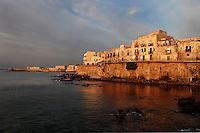 General view of Lungomare d'Ortigia, Syracuse, Sicily,  with Castello Maniace in the distance, pictured on September 14, 2009, glowing in the dawn light which casts reflections in the sea. The island Ortigia is the historic centre of Syracuse. Today the city is a UNESCO World Heritage Site. Picture by Manuel Cohen.