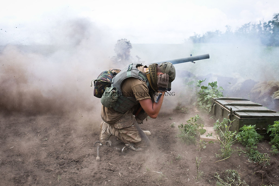 UKRAINE, Shyrokyne: Lenza shooting with the anti-tank grenade launcher. Next to him, his comrade Andrei is blocking his ears. <br /> <br /> UKRAINE, Shyrokyne: Lenza tire &agrave; l'aide du lance grenades antichar. A c&ocirc;t&eacute; de lui, son camarade Andrei bouche ses oreilles.