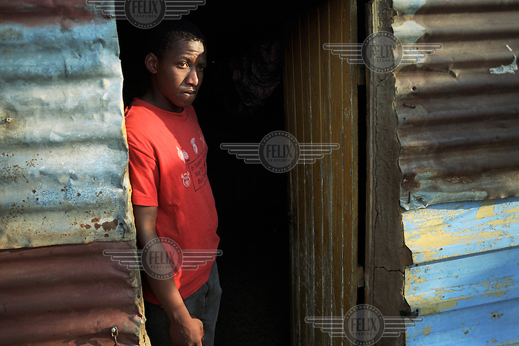 Young carer Joseph Nhlapo stands in the doorway of his home. Joseph helps to take care of his ailing mother who is HIV positive.