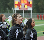 0875                                   Megan Miles and the Eagle River cheerleaders perform in a rainstorm at halftime of the Wolves-Wasilla football game Friday, Aug. 18, 2017.  Photo for the Star by Michael Dinneen
