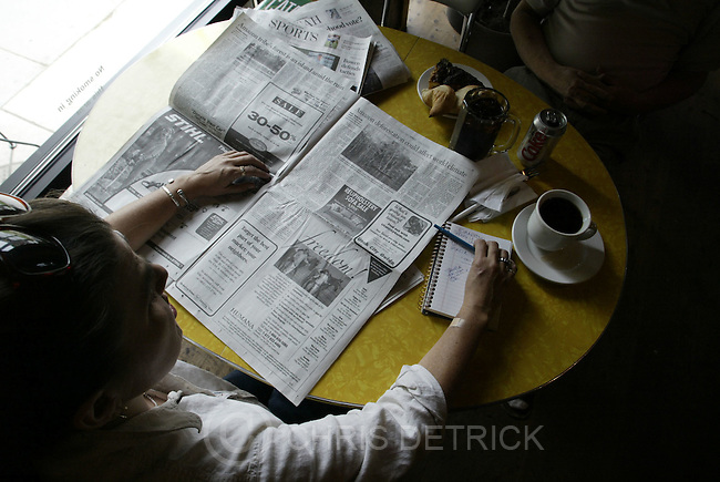 Salt Lake City, UT--16 Jun 2005--.Brinda Valdez, of Salt Lake City, reads a copy of The Tribune at The Coffee Garden while enjoying a cup of coffee..Chris Detrick /Salt Lake Tribune.File #Trib Readers CD12