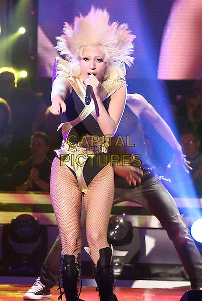 LADY GAGA (Stefani Germanotta).performs during the Italian TV Show 'Quelli Che il Calcio' in Milan, Italy, .27th April 2009. .concert tv performance gig on stage performing full length black gold leotard microphone tights fishnet  belt fringe knee high boots dancing hair funny singing .CAP/ADM/LIV.©Antonio Sorano/Liverani/Admedia/Capital Pictures