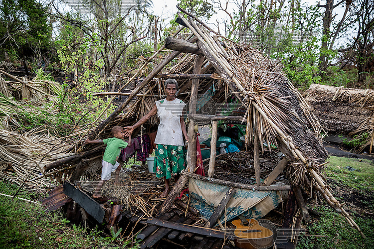 Jacklyn Kawira (63), a local prophet and a member of the 'Unity' cargo cult sect, stands in the ruins of her destroyed house with her grandson Jackson David (5). Their village was badly damaged by Cyclone Pam. <br /> Fallen trees are visible near Port Vila on Efate Island. <br /> Cyclone Pam, a tropical storm that hit the Pacific island nation of Vanuatu on 13 March 2015, is considered one of the worst natural disasters to affect the country. Over 15 people died in the storm and winds up to 165 mph (270 km/h) caused widespread damage to houses and infrastructure.