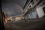 Boys playing baseball in the street in Santiago de Cuba.