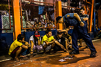 "MANILA, PHILIPPINES - SEPTEMBER 30: A police officer talks down to a known drug target, Moises ""Momoy"" Palawal, captured with the methamphetamine sachets, cash and other drug accessories, during a ""one time big time"" police operation, on September 30, 2016 in the neigborhood of Tondo in Manila City, Philippines. The One Time Big Time operations, involving over 100 police officers, are designed to capture suspected drug dealers and also a process large group of youths in violation of a civil ordinance order to ascertain if they have any outstanding court orders. <br /> Photo by Daniel Berehulak for The New York Times"