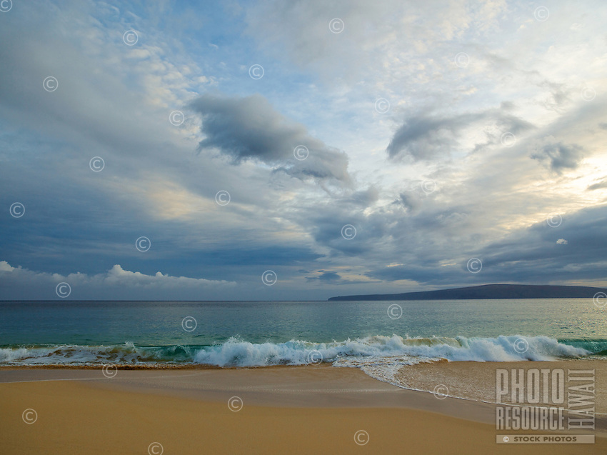 Big Makena beach, with smooth sand and gentle green waves beneath textured clouds, Maui.