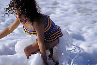 A young girl plays joyfully in the sea foam by the ocean's edge at the beach on the north shore of Oahu.