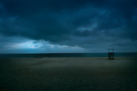 Lifeguard stand on an empty beach as storm approaches.