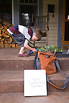 """Andrew and Patricia Nimelman cosult with Donna Smith (otherwise known as """"Your Backyard Farmer) at their home in NE Portland, OR.  Their son watering the vegetable starts on the front porch."""