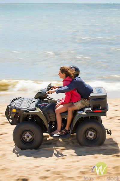 Hammonasset Beach State Park, New Haven County, Madison, Connecticut. Couple riding ATV on beach