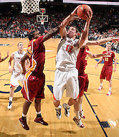 Dec. 30, 2010; Charlottesville, VA, USA; Virginia Cavaliers guard Joe Harris (12) shoots the ball between Iowa State Cyclones forward Calvin Godfrey (15) and Iowa State Cyclones forward Jamie Vanderbeken (23) during the game at the John Paul Jones Arena. Iowa State Cyclones won 60-47. Mandatory Credit: Andrew Shurtleff-