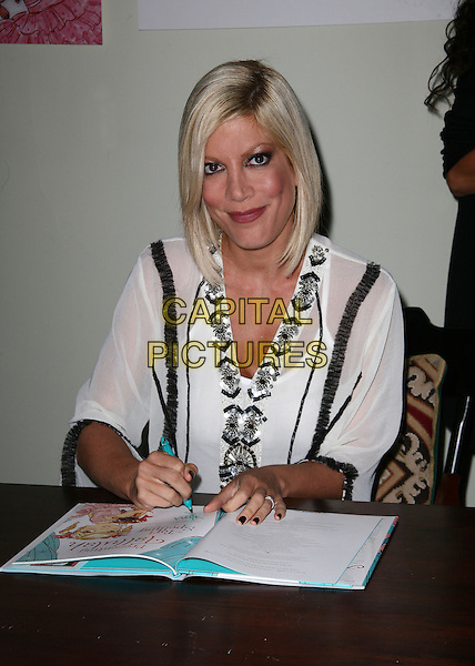"TORI SPELLING.Tori Spelling signs copies of her new book ""Presenting Tallulah"" at Book-Ends Book Store, Ridgewood, New Jersey, USA..September 21st, 2010.half length  black white sheer table sitting.CAP/ADM/PZ.©Paul Zimmerman/AdMedia/Capital Pictures."