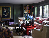 The library's sofa by Restoration Hardware is covered in a Perennials fabric, the vintage club chairs, upholstered in a Great Plains linen, are from Duane, the cocktail table is Chinese, the circa-1960 chair is by Milo Baughman, and the stool came from the former Manhattan nightclub Moomba; the 18th-century English portrait is a family heirloom, the zebra skin is antique, the blinds are by Hunter Douglas, and the walls are painted in Dragon's Breath by Benjamin Moore.