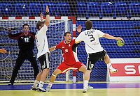 11 JUN 2010 - LONDON, GBR - Great Britain's Daniel McMillan (red - #18) watches as Estonian Risto Lepp (white and black) prepares to shoot during the two teams 2012 European Handball Championships Qualification Tournament match (PHOTO (C) NIGEL FARROW)