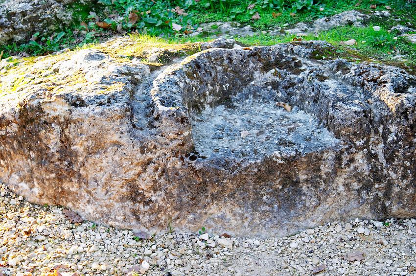 An ancient druid sacrifice sacrificial throne chair in the garden at Chateau Belingard in autumn evening sunshine Chateau Belingard Bergerac Dordogne France