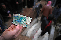 SYRIA, 02.2012, village of Kureen, Idlib province. © Timo Vogt/EST&OST. A man shows an Iranian bill found after the raid by Syrian govenment forces. The people take this as an evidence for the involvement of Iranian counter-revolutionaries in Syria. About two thousand inhabitants gather for the funeral of four men and one woman killed the day before during a full scale military attack on the village. On February 22 the Syrian army attacked the village. Kureen was among the first villages in the northwest of Syria controlled by the opposition. Some villagers and members of the defence units escaped to surrounding olive orchards when the attack began in the early morning. A majority of the inhabitants didn´t manage to escape. The heavy shelling lasted 7 hours. Soldiers searched all houses, burnt some of them down, looted shops, stole cars and furniture. About 60 motorcycles were destroyed. Tanks demolished several houses. 6 men were executed. One woman died as a result of an heart attack.