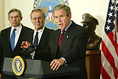 United States President George W. Bush (R) speaks next to US Secretary of Defense Donald Rumsfeld (C) and US Deputy Secretary of Defense Paul Wolfowitz (L) during a visit at the Pentagon March 25, 2003 in Arlington, Virginia. Bush asked Congress for a wartime supplemental appropriations of $74.7 billion to fund needs directly arising from the war in Iraq and the global war against terror.   <br /> Credit: Alex Wong / Pool via CNP