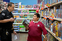 STAFF PHOTO JASON IVESTER --12/09/2014--<br /> Benton County Dep. Joe Pruitt talks with Benny Valdez, 9, of Rogers while shopping for clothes and toys on Tuesday, Dec. 9, 2014, inside the Wal-Mart Supercenter on Pleasant Crossing Boulevard in Rogers. Members of the Benton County Sheriff's Office helped the children pick out clothes and toys with a $150 budget each as part of the department's annual Shop With a Cop program.