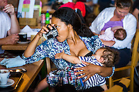 A mother drinking a cup of tea or coffee while breastfeeding in a cafe. Big Latch On event,